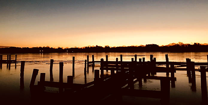 Photo of empty docks backlit by the sunrise.