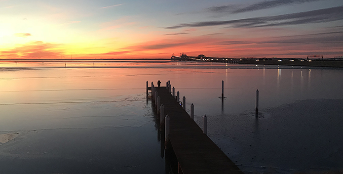 Photo of the Chesapeake Bay at sunset with the Bay Bridge in the background.