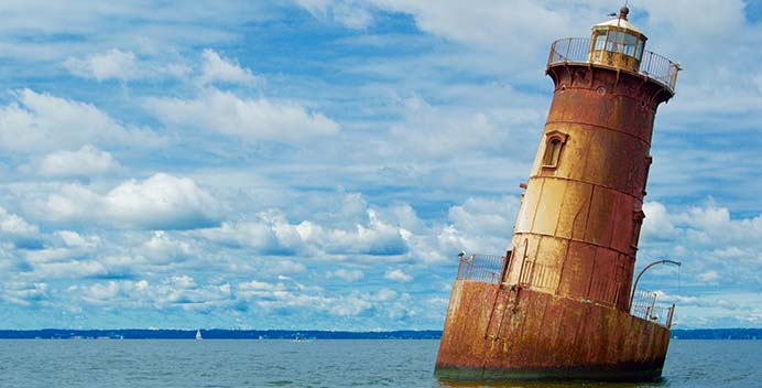 A photo of an abandoned lighhouse rusting in the water.