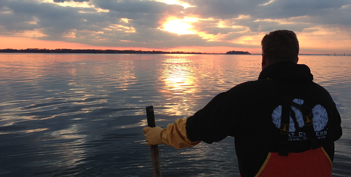 Photo of a waterman oystering as the sun rises over the Bay.