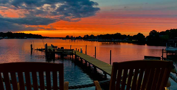 A fiery sun sets over Lake Ogleton with Adirondack chairs in the foreground