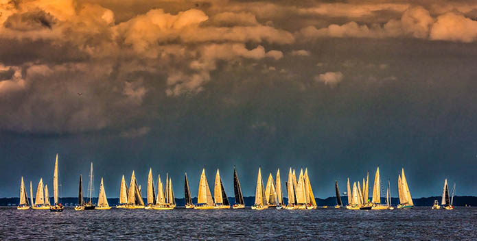Photo of sailboats on the water against a backdrop of clouds lit by the setting sun.
