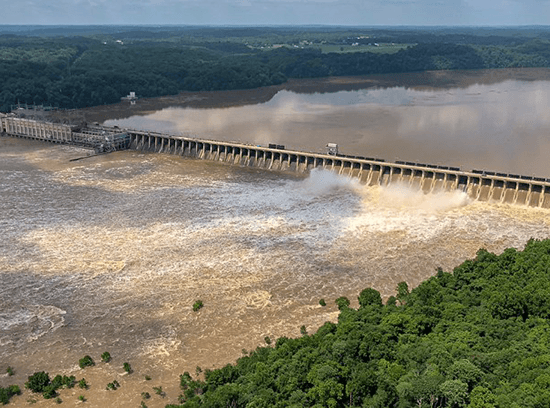 Muddy water pours through the Conowingo Dam, flooding the forest below.